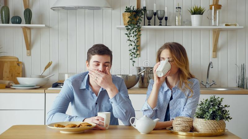Sad couple girl guy have breakfast drinking tea silently royalty free stock photo