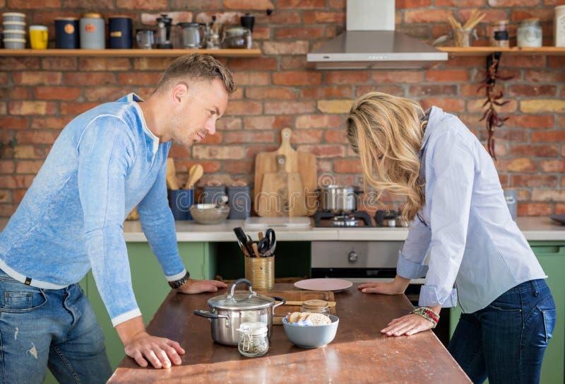 Sad couple having argument in kitchen royalty free stock photo