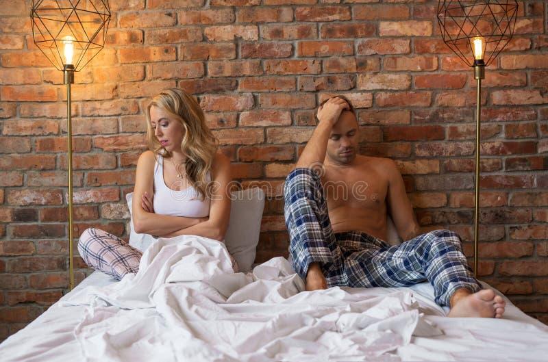 Sad couple having problems in bedroom stock image