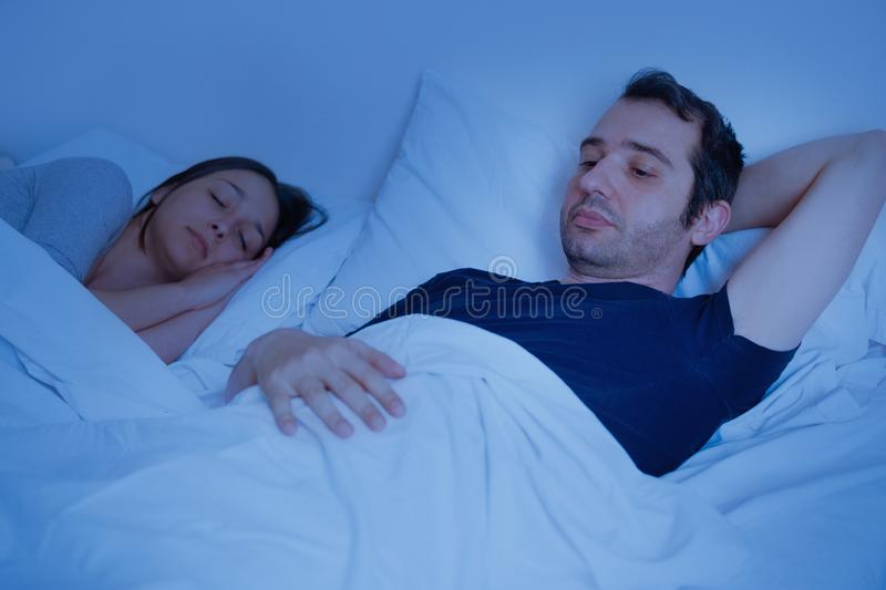 Sad couple and relationship difficulties in bed. Relationship bed problem and couple ling in bed stock photos