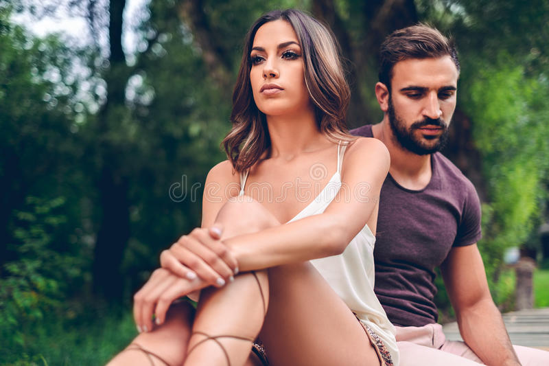 Sad couple sitting in the park stock photo