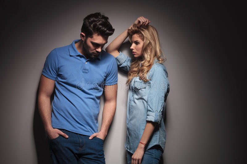 Sad couple standing next to each other. In studio, men looking down stock photography