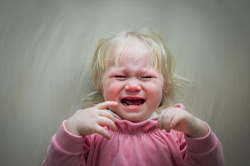 Sad crying baby girl, child in pain, kid stress stock image