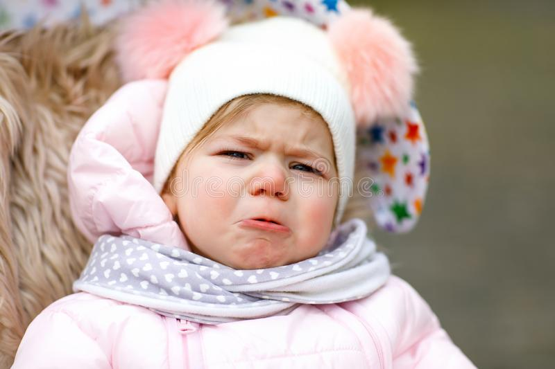 Sad crying hungry baby girl sitting in the pram or stroller on cold day stock image