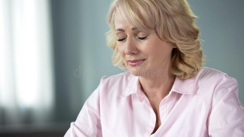 Sad crying lady with closed eyes remembering youth and health moments, aging. Stock photo royalty free stock image