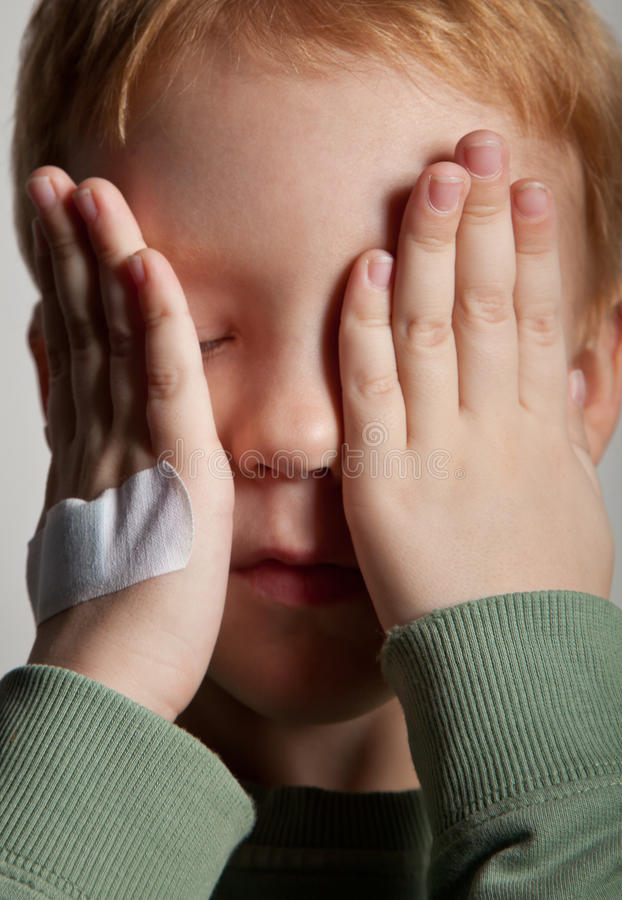 Sad crying little boy covers his face with hands. BW portrait of sad crying little boy covers his face with hands. One hand with medical plaster royalty free stock photography