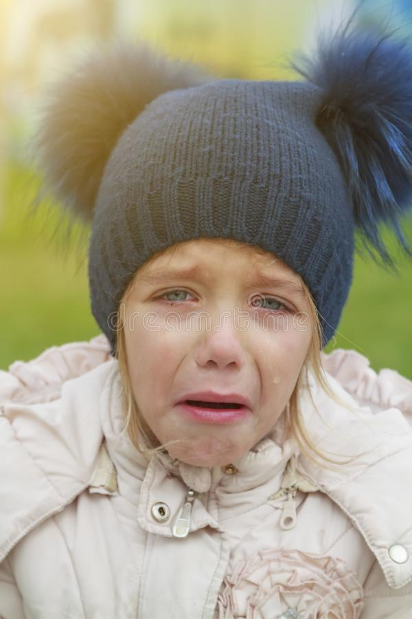 Sad crying offended girl cold autumn outdoor. Concept of upset child royalty free stock photo