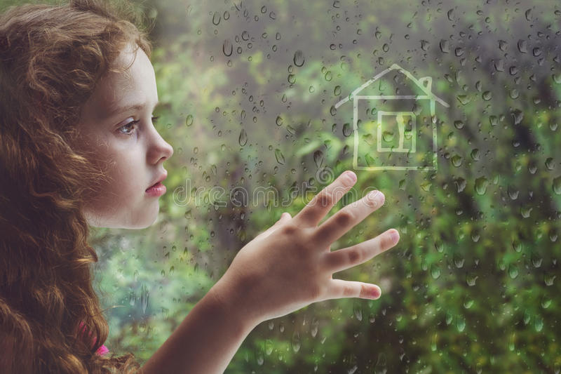 Sad curly little girl looking out the rain drop window stock images