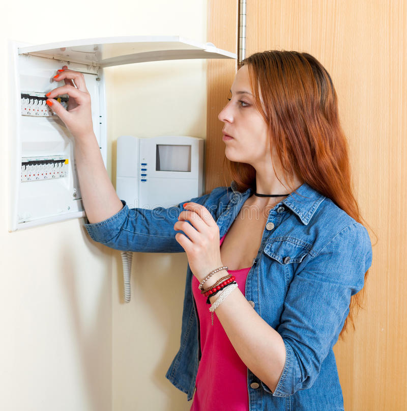 Sad cute woman near power control panel stock photo