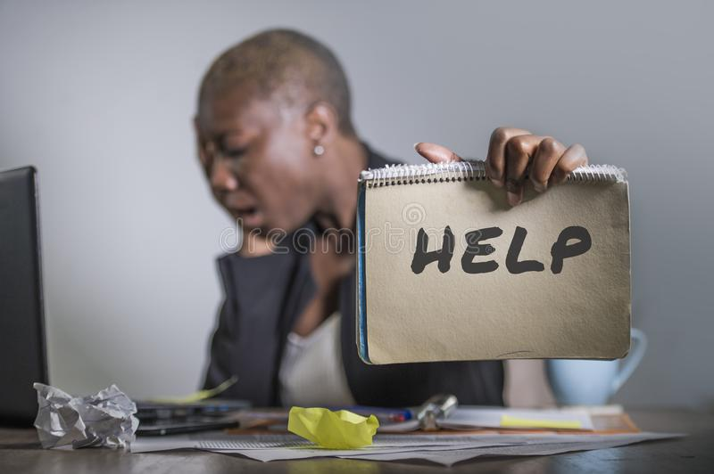 Sad and depressed black afro American woman suffering stressed at office working with laptop computer feeling overwhelmed asking f. Or help holding notepad in stock images