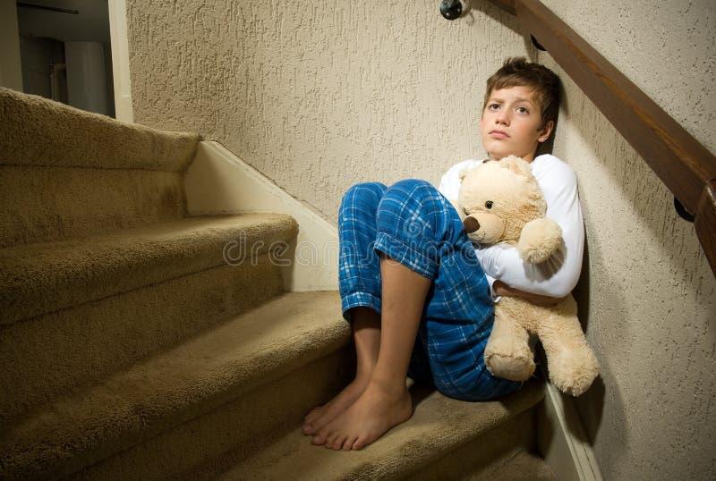 Sad and depressed boy in corner stock photos