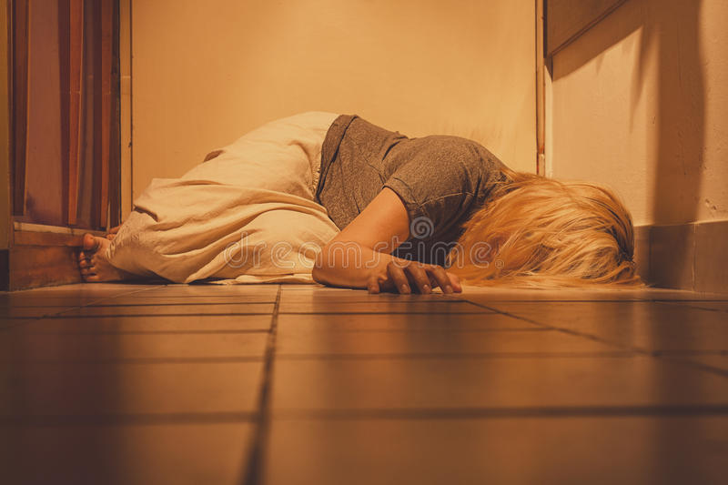 Sad, depressed and lonely woman lying on a floor tiles, in a skirt, barefoot royalty free stock image