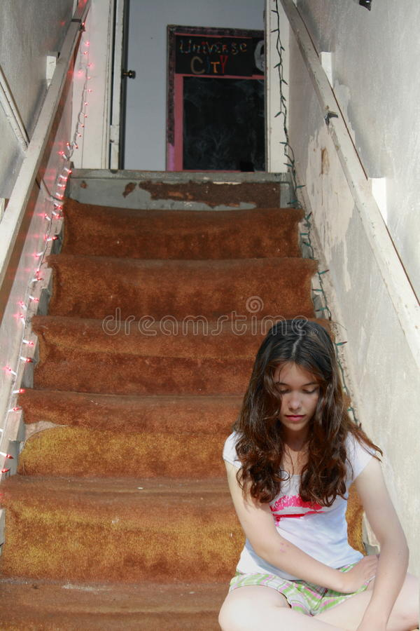 Sad depressed teen girl on stairs. Young sad teen girl depressed on stairs royalty free stock photo
