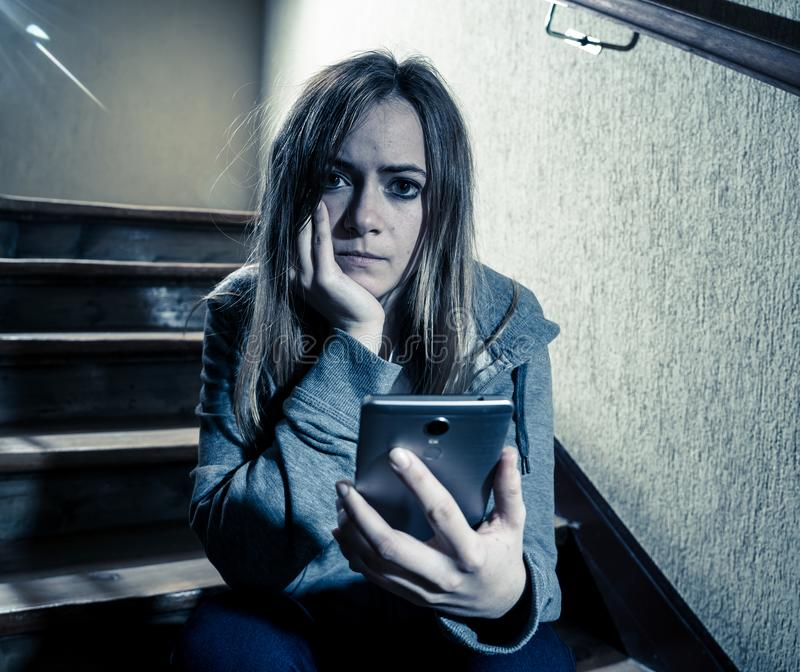 Sad depressed unhappy teenager girl suffering from cyberbullying by mobile smart phone sitting alone stock images