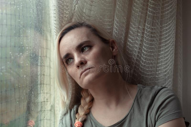 Sad, depressed woman sitting by the window, looking longingly out royalty free stock photography