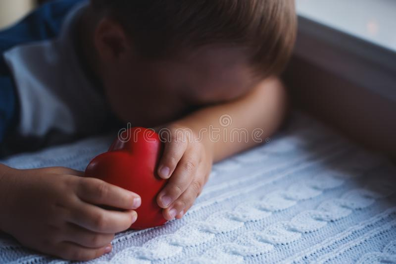 Sad and desperate child boy holding red toy heart in hands and hiding his face royalty free stock images