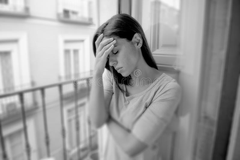 Sad desperate hispanic girl at home balcony looking depressed suffering terrible migraine headache disorder or depression. Black and white portrait young sad royalty free stock photo