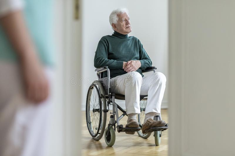 Sad disabled elderly man in the wheelchair in the hospital. Blurred nurse in a foreground royalty free stock image
