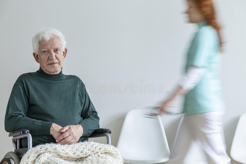 Sad disabled elderly man in green sweater in a hospital and blur. Sad disabled elderly men in green sweater in a hospital and blurred nurse walking behind him stock photos