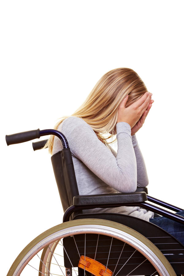 Sad disabled woman crying. Young sad disabled woman in wheelchair crying royalty free stock image