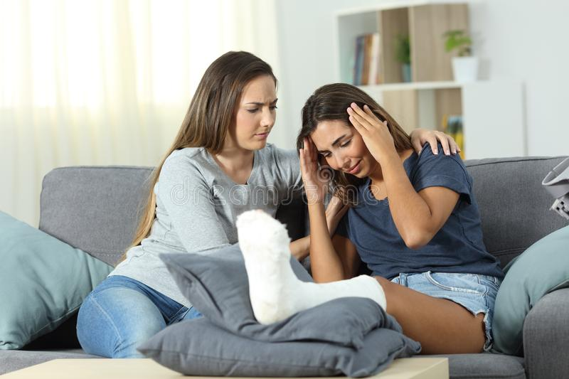 Sad disabled woman and friend comforting her stock image