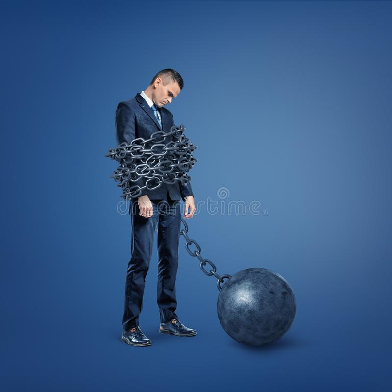 A sad disappointed businessman stands bound by a wide metal chain which is locked to an iron ball. stock images
