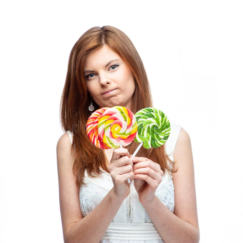 Sad, disappointed girl with candy. Isolated on white background stock photography