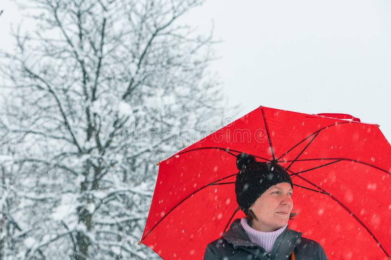 Sad disappointed woman in snow under umbrella. Sad disappointed woman in standing in winter snow under big red umbrella royalty free stock photography