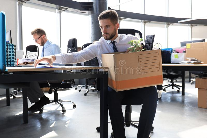 Sad dismissed worker are taking his office supplies with him from office royalty free stock photos