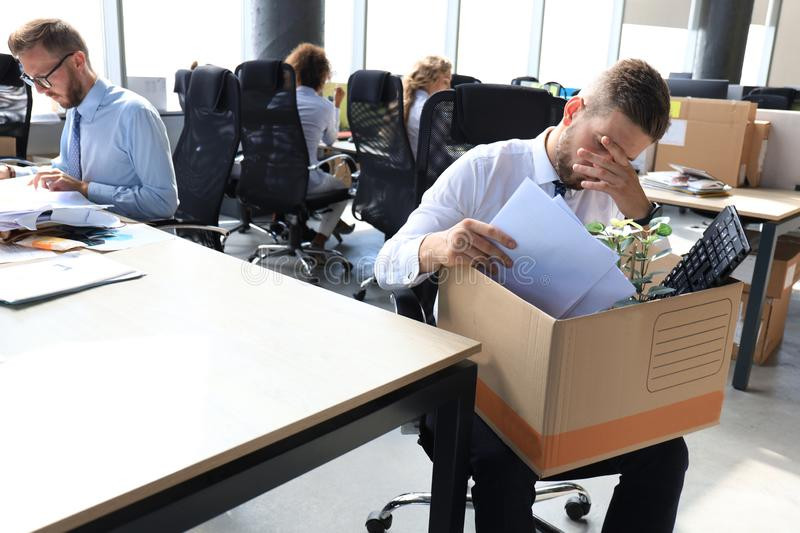 Sad dismissed worker are taking his office supplies with him from office stock photo