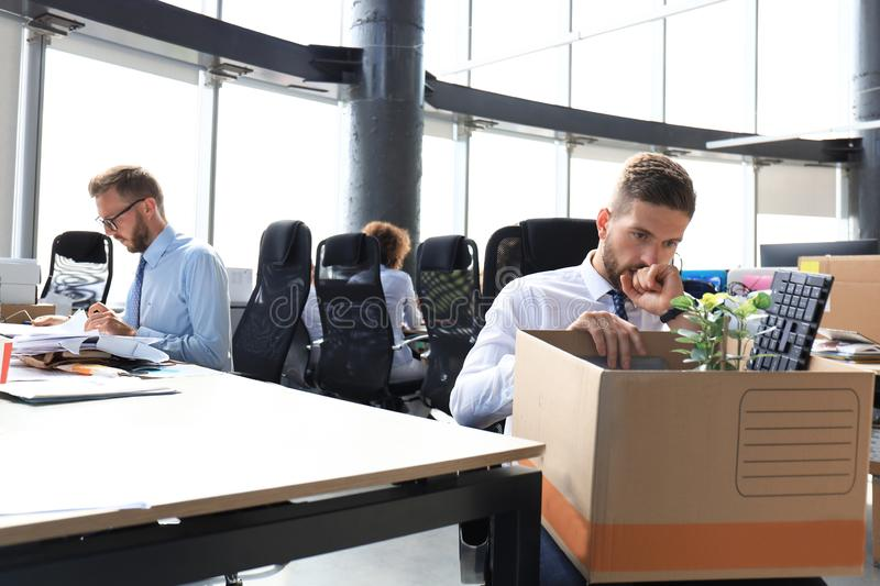 Sad dismissed worker are taking his office supplies with him from office royalty free stock image