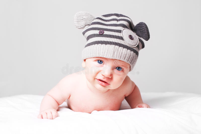 Sad dissatisfied little baby boy. Sad, dissatisfied little baby boy lying on bed and looking into camera stock photo