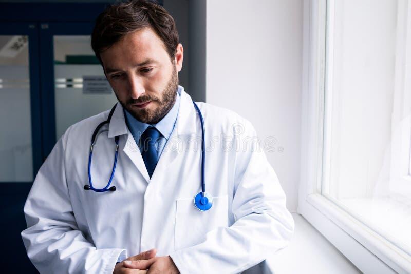Sad doctor standing in corridor royalty free stock image