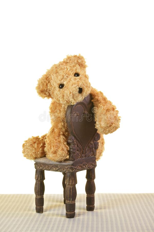 Sad depressed Teddy bear sitting on chair royalty free stock photos