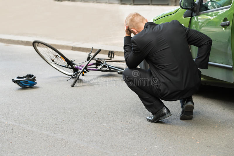 Sad driver after collision with bicycle stock images