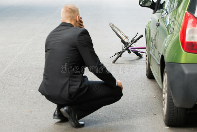 Sad driver after collision with bicycle. Sad Male Driver After Collision With Bicycle On Road royalty free stock photography