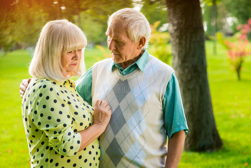 Sad elderly couple outdoor. Man next to a woman. What are you worried about. Truth is bitter stock photo