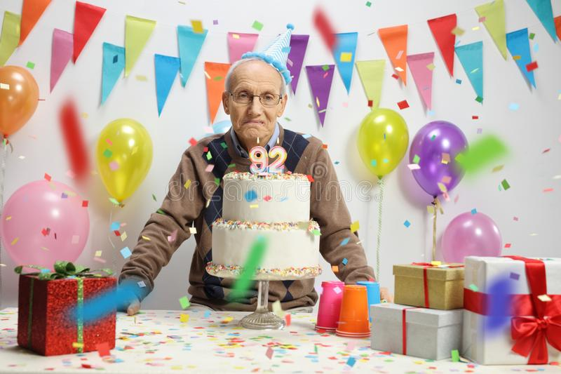 Sad elderly man with a birthday cake. Against a wall with decorations royalty free stock images