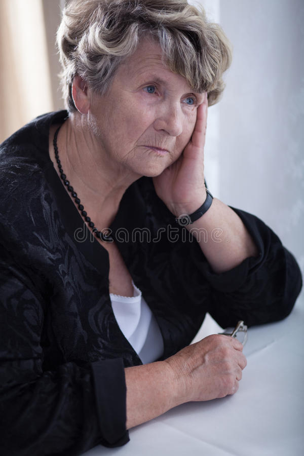 Sad elderly woman stock photos
