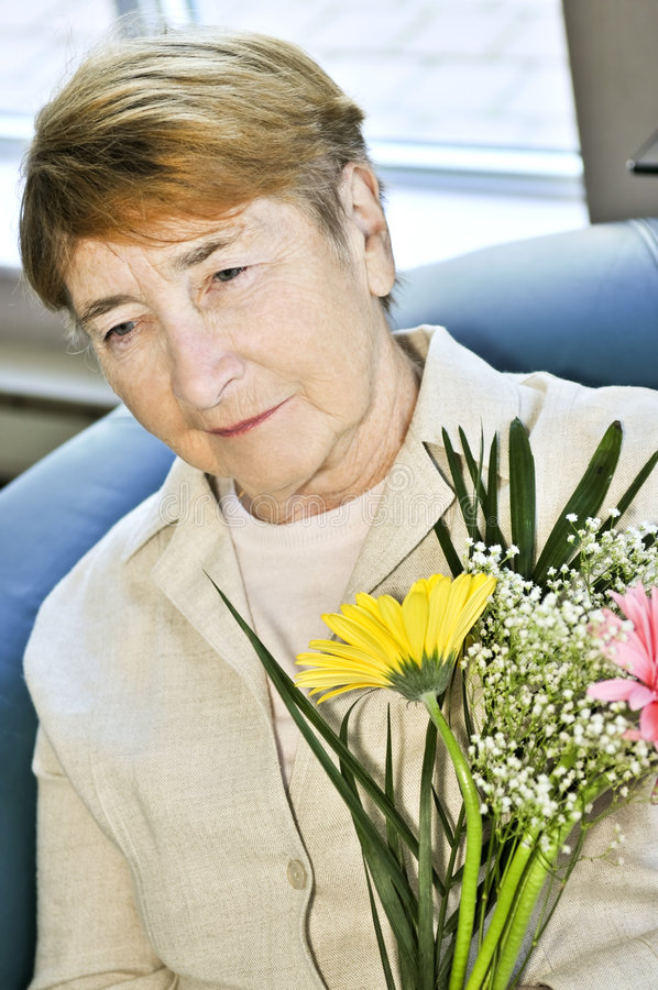 Sad elderly woman with flowers royalty free stock photos
