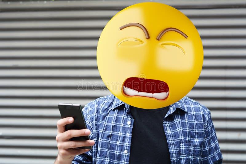 Sad emoji head man. Sad Emoji head man using a smartphone. Emoji concept royalty free stock images