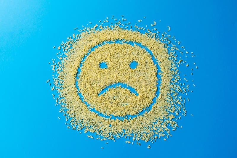 Sad emoji smile on a blue background. Smiley from yellow sugar grains. Stock image. Sad emoji smile on a blue background. Smiley from yellow sugar grains royalty free stock images