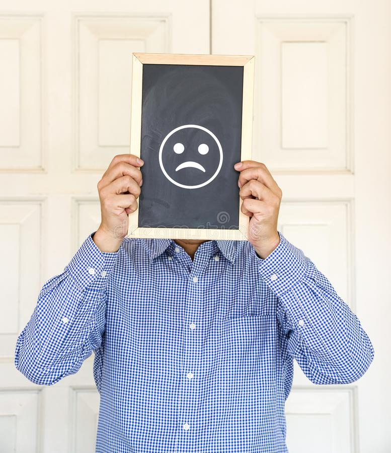 Sad emoticon on the board in front of a man`s face royalty free stock photo