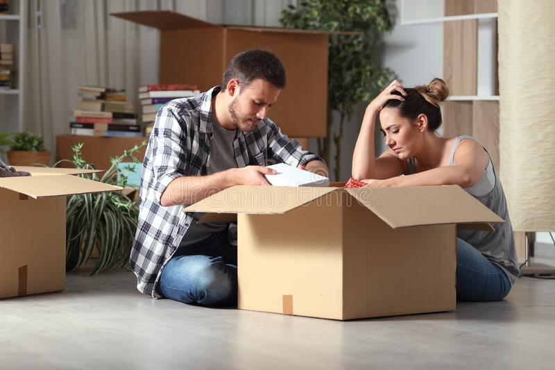 Sad evicted couple moving home boxing belongings in the night stock photos