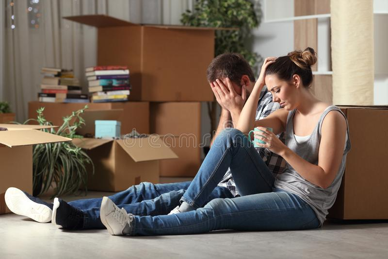 Sad evicted couple moving home complaining on the floor royalty free stock images