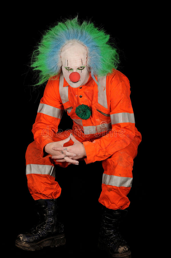 Sad Evil Clown. Sad, evil clown in safety orange costume on black background royalty free stock photo