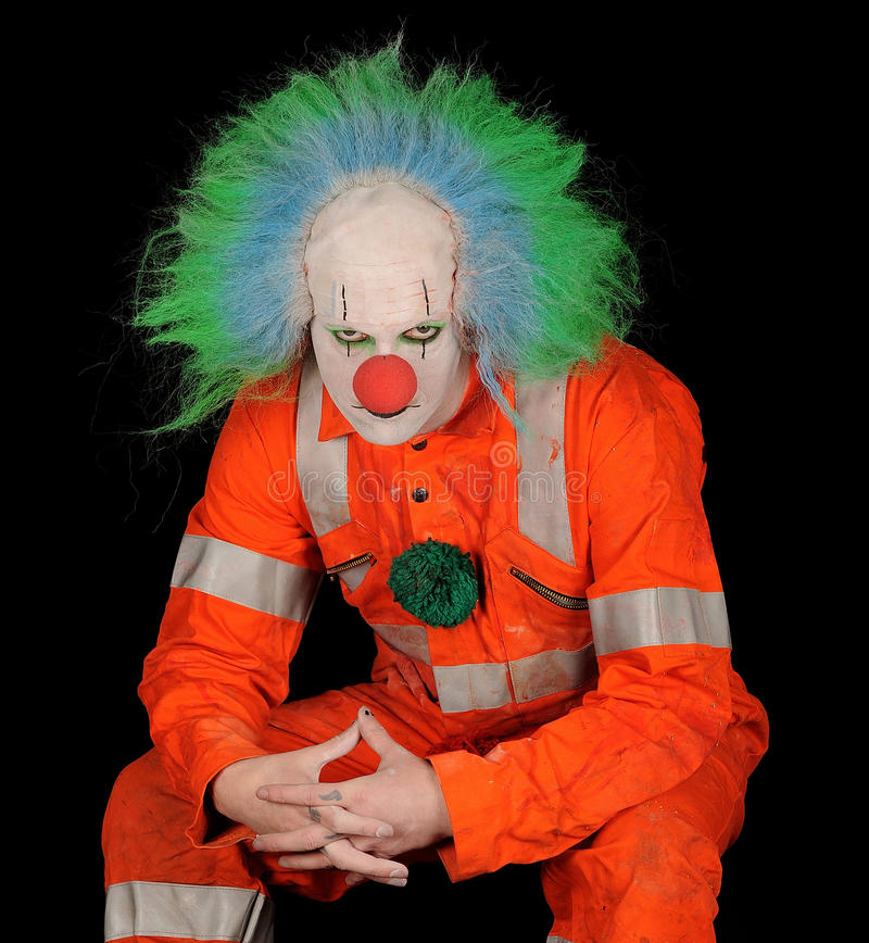 Sad Evil Clown. Sad, evil clown in safety orange costume on black background royalty free stock photography