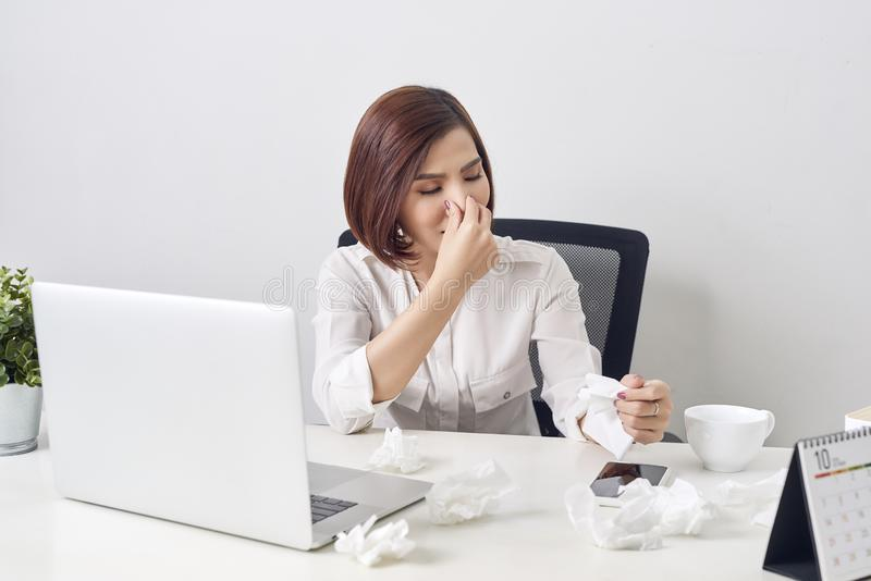 Sad exhausted woman with tissue suffering from cold while working with laptop at table stock photography