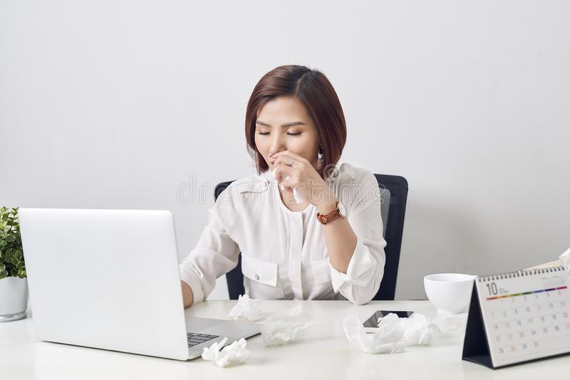Sad exhausted woman with tissue suffering from cold while working with laptop at table.  stock image