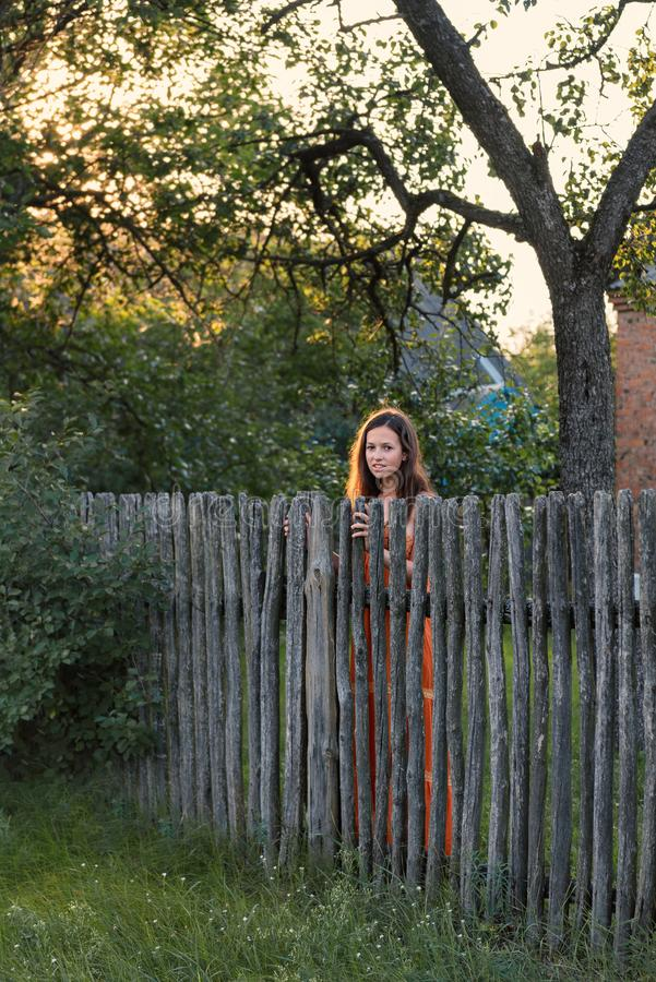 A sad expectant girl stands behind a wooden palisade in a village attire. A sad expectant young woman stands behind a wooden palisade in a village attire royalty free stock photos